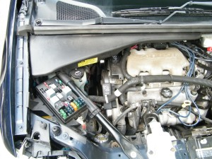 Top cover near passenger side window covering battery